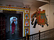 Woman entering the courtyard of a traditional house with a painting of a Mughal King riding an elephant on 20th January 2018  in the city of Udaipur, India. Throughout the ages Indian artists have shown a strong affinity for decorated elephants from miniatures to huge street murals.