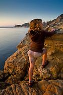 Young girl climbing on shoreline rocks at Morro Bay State Park, Morro Bay, California