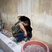 August 10, 2012 - Aleppo, Syria: A Free Syria Army (FSA) fighter advances towards the frontline through a hole in a wall of a house in Saheledine, a strategic neighborhood in southwest Aleppo...The Syrian Army have in the past week increased their attacks on residential neighborhoods where Free Syria Army rebel fights have their positions in Syria's commercial capital, Aleppo.