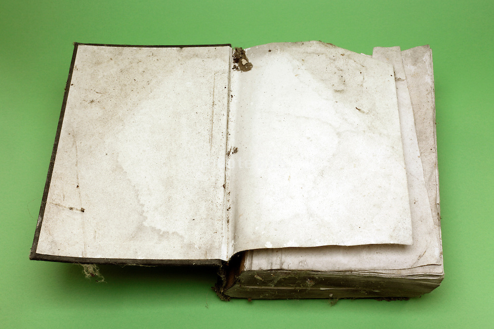 water and time damaged hardcover book open on the first blank page
