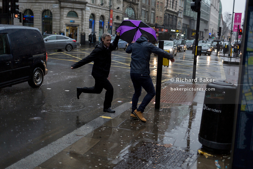 Storm Georgina swept across parts of Britain and in central London, lunchtime office workers were caught out by torrential rain and high winds, on 24th January 2018, in London, England. Pedestrians resorted to leaping across deep puddles at the junction of New Oxford Street and Kingsway at Holborn, the result of overflowing drains. Fifth in a sequence of seven photos.