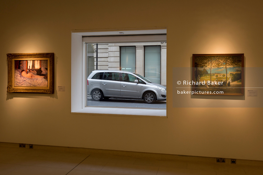 A parked car framed inside the window of art auctioneers Christie's, on 19th November 2017, in London, England.