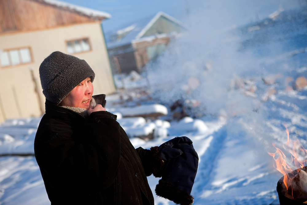 The Pole of Cold - local inhabitant burning outside paper at the village of Tomtor. The area is extremely cold during the winter. Two towns by the highway, Tomtor and Oymyakon, both claim the coldest inhabited place on earth (often referred to as -71.2°C, but might be -67.7°C) outside of Antarctica. The average temperature in Oymyakon in January is -42°C (daily maximum) and -50°C (daily minimum). The images had been made during an outside temperature in between -50°C up to -55°C. Tomtor, Jakutien, Yakutia, Russian Federation, Russia, RUS, 19.01.2010