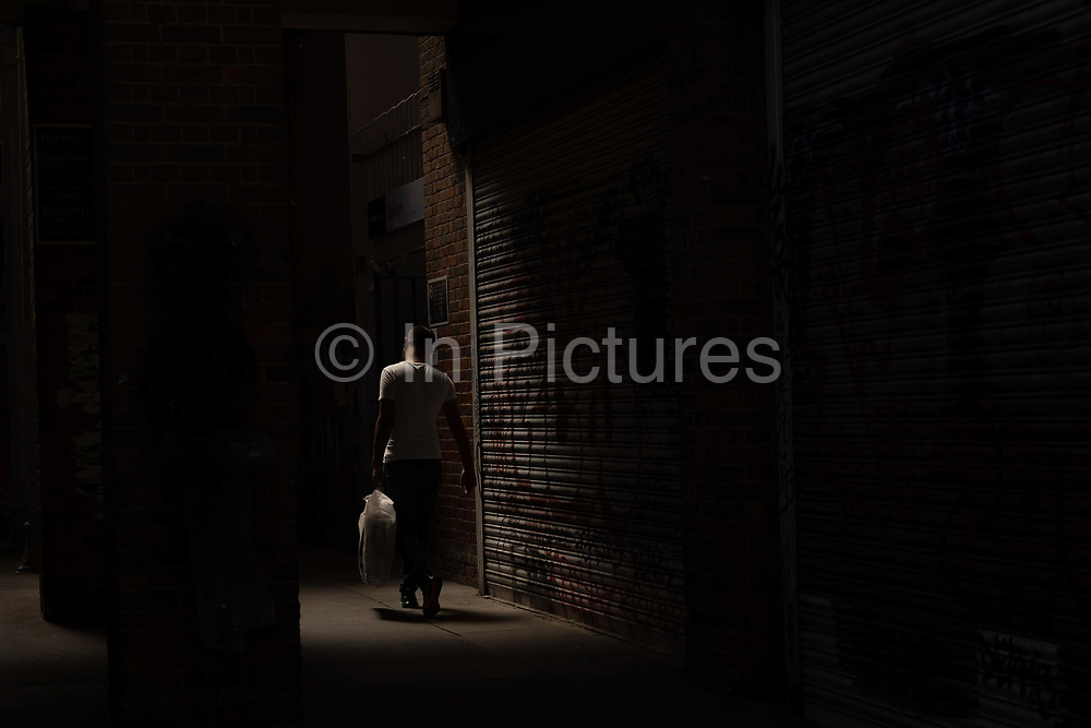 A man walking between the shadows at Brixton Railway Station as temperatures reach the low 30s across the capital on the 24th July 2019 in South London in the United Kingdom.