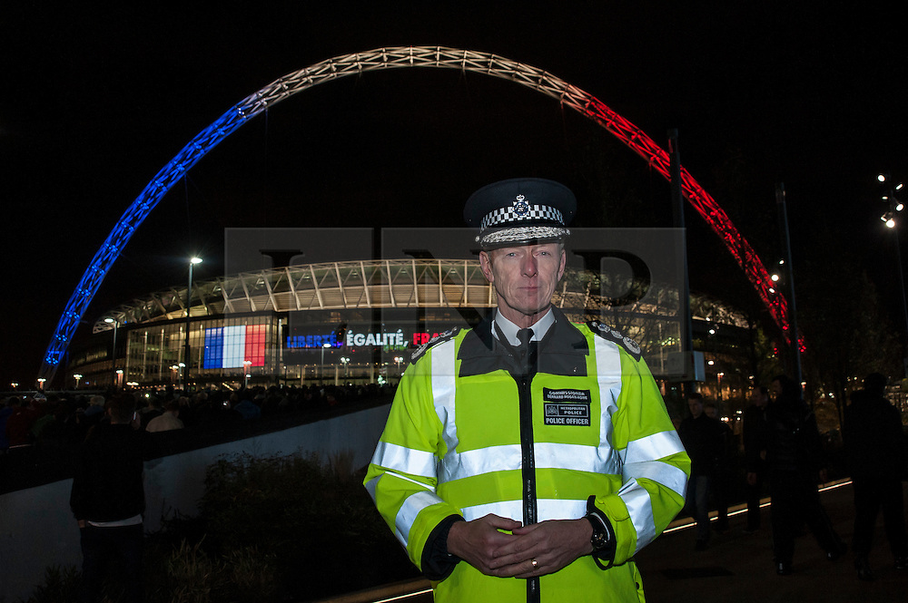 """© Licensed to London News Pictures. 17/11/2015. LONDON, UK. Metropolitan Police Commissioner, Sir Bernard Hogan-Howe, stands outside Wembley Stadium ahead of the football friendly between England and France. The stadium is illuminated with the French colours, and the words """"Liberté, Égalité, Fraternité"""".  Photo credit : Stephen Chung/LNP"""