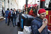 Man wearing Beats headphones and a New York baseball cap speaking into his mobile phone in Piccadilly in London, England, United Kingdom.