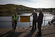 Islander Com McNicholl (left) chatting to GP Dr David Binnie whilst waiting for the arrival of the Caledonian MacBrayne ferry at Scalasaig from Oban on the the Inner Hebridean island of Colonsay on Scotland's west coast.  The island is in the council area of Argyll and Bute and has an area of 4,074 hectares (15.7 sq mi). Aligned on a south-west to north-east axis, it measures 8 miles (13 km) in length and reaches 3 miles (4.8 km) at its widest point, in 2019 it had a permanent population of 136 adults and children.