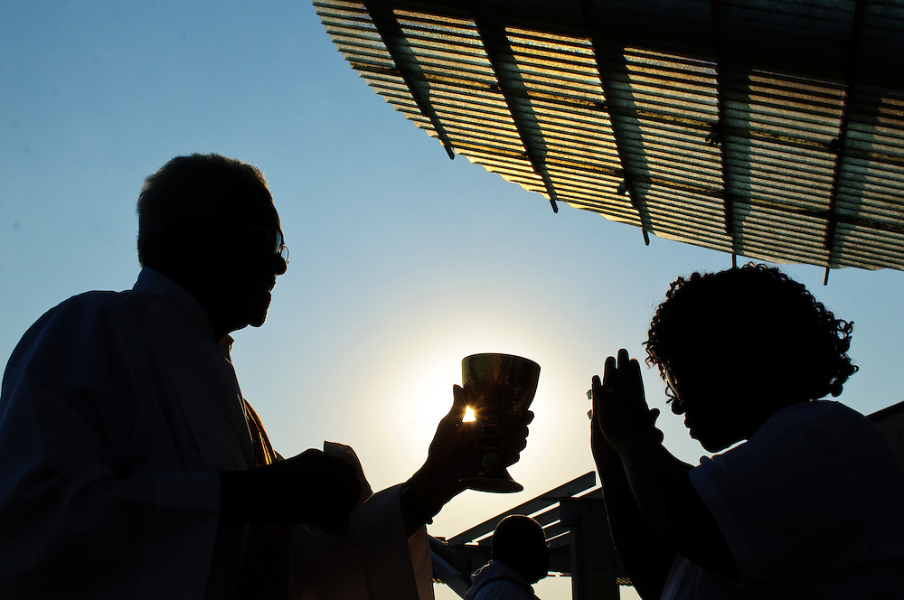 Deacon Leonard Richardson distributes communion at Rainbow Beach on the city's south side during a sunrise mass to pray for non-violence during the upcoming school year. The event hosted by The Black Catholic Deacons in the Archdiocese of Chicago is one of six simultaneous masses along Chicago's lakefront. August 25, 2012 l Brian J. Morowczynski/ViaPhotos.