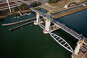 Nederland, Zuid-Holland, Botlek, 19-09-2009; Functioneringssluiting Hartelkering, de waterkering in het Hartelkanaal  wordt een maal per jaar, voordat het stormseizoen begint, getest. Tijdens  het sluiten van de kering ligt alle scheepvaartverkeer naar de Rotterdamse haven stil. .Detail van de kering met schutsluis..De kering sluit normaal gesproken alleen bij dreigende stromvloed en bij een waterstand van 3 meter of meer boven NAP. De kering, onderdeel van de Deltawerken, vormt samen met de Maeslantkering  de Europoortkering en beschermt Rotterdam en achterland bij extreme waterstanden. .Netherlands, Rotterdam harbour. Aerial view of one of the two storm surge barriers. This barrier, the Hartelkering  in the Hartel canal, together with the greater nearby  Maeslant barrier (in the New Waterwy), are tested during the so-called functioning closure, taking place one a year before the storm season begins. The waterway and canal, leading to the Port of Rotterdam, are closed during the test..luchtfoto (toeslag), aerial photo (additional fee required).foto/photo Siebe Swart