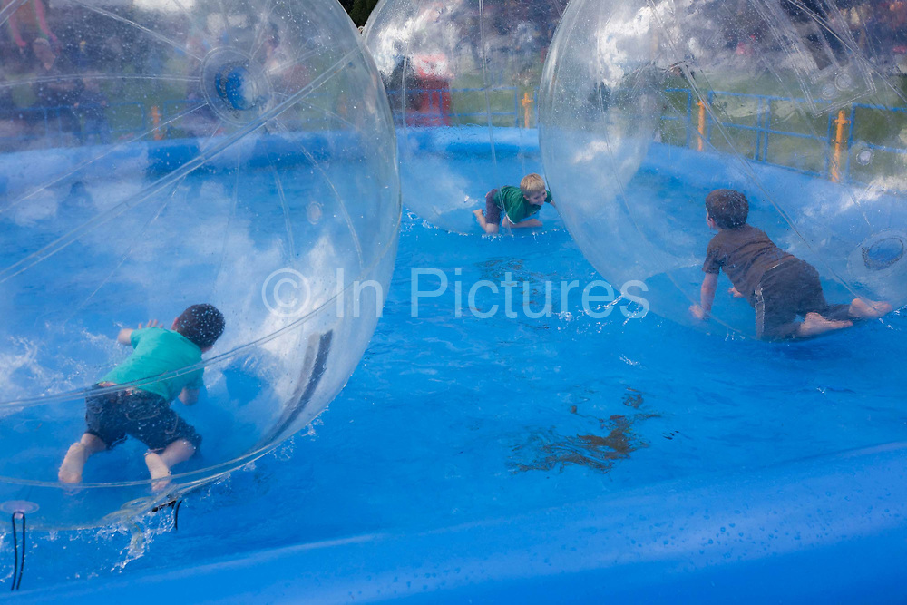 Children roll around the inside of Water Balls at the south London Lambeth Country Fair. A water ball is a large inflatable sphere that allows a person to walk across a water surface. The water ball is similar to a zorb (rolling downhill in an orb, generally made of transparent plastic), but this has only one layer and is designed for water travel rather than downhill rolling. The giant ball is usually two metres in diameter and has a zippered entrance to allow for easy entry and exit. It stores flat and weighs 15 kilograms. The best water balls are constructed from polyvinyl chloride (PVC) 0.6–0.7mm thick. http://en.wikipedia.org/wiki/Water_ball