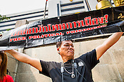 """23 JANUARY 2013 - BANGKOK, THAILAND:   A man holds up a banner calling for the release of political prisoners after Somyot Prueksakasemsuk was sentenced on """"Lese Majeste"""" charges Wednesday. Somyot was sentenced to 11 years imprisonment Wednesday. He was arrested on April 30, 2011, and charged under article 112 of Thailand's penal code, which states that ?whoever defames, insults or threatens the King, the Queen, the Heir-apparent or the Regent, shall be punished with imprisonment of three to fifteen years"""" after the magazine he edited, """"Red Power"""" (later changed to """"The Voice of Thaksin"""") published two articles by Jit Pollachan, the pseudonym of Jakrapob Penkair, the exiled former spokesman of exiled fugitive former Prime Minister Thaksin Shinawatra. Jakrapob, now living in Cambodia, has never been charged with any crime for what he wrote.     PHOTO BY JACK KURTZ"""