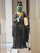Stoneware figure from a judgement group with aubergine, green, ochre and straw glazes.  Ming Dynasty, 16th century AD.  The belief in Hell entered China with Buddhism during the early 1st millennium AD.  From the late Tang Dynasty judgement scenes in the underworld were common.  This figure of a judge's assistant is holding records of evil deeds under his left arm.