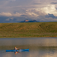 A youngster fishes from a kayak on Wyoming ranch pond.