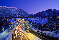 Lorimer Road is lit with Christmas lights in Whistler, BC. Whistler Mountain and Blackcomb Mountain rise in the distance.