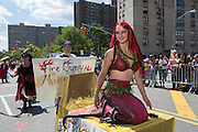 A mermaid in a red scaly costume rides a float through the parade.