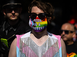 """© Licensed to London News Pictures . 28/08/2021. Manchester, UK. A protester wearing a """" Pride is a protest """" face mask at the demo . People take part in a Reclaim Pride march through Manchester City Centre , in opposition to the management of the city's """"official"""" Manchester Pride charity festival . The Manchester Pride charity parade was cancelled in 2020 due to Coronavirus . An """"equality march"""" organised by Manchester Pride charity was due to take place on Deansgate as the protest passed through the Gay Village . Protesters object to Manchester Pride charity's withdrawal of funding for the LGBT Foundation's condom distribution scheme and HIV charity George House Trust as well as increasing commercialisation of the annual event . Photo credit: Joel Goodman/LNP"""