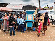02 AUGUST 2015 - BHAKTAPUR, NEPAL:  People buy snacks from a street vendor in front of a small Internal Displaced Person (IDP) camp at Durbar Square in Bhaktapur for people left homeless by the Nepal earthquake. The Nepal Earthquake on April 25, 2015, (also known as the Gorkha earthquake) killed more than 9,000 people and injured more than 23,000. It had a magnitude of 7.8. The epicenter was east of the district of Lamjung, and its hypocenter was at a depth of approximately 15 km (9.3 mi). It was the worst natural disaster to strike Nepal since the 1934 Nepal–Bihar earthquake. The earthquake triggered an avalanche on Mount Everest, killing at least 19. The earthquake also set off an avalanche in the Langtang valley, where 250 people were reported missing. Hundreds of thousands of people were made homeless with entire villages flattened across many districts of the country. Centuries-old buildings were destroyed at UNESCO World Heritage sites in the Kathmandu Valley, including some at the Kathmandu Durbar Square, the Patan Durbar Squar, the Bhaktapur Durbar Square, the Changu Narayan Temple and the Swayambhunath Stupa. Geophysicists and other experts had warned for decades that Nepal was vulnerable to a deadly earthquake, particularly because of its geology, urbanization, and architecture.      PHOTO BY JACK KURTZ
