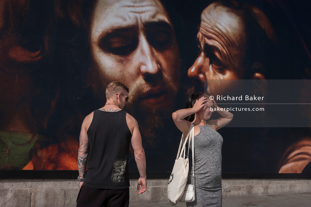 A young couple beneath the faces from The Taking of Christ (c1602) the painting of the arrest of Jesus, by Italian Baroque master Caravaggio and exhibited at the National Gallery, London.