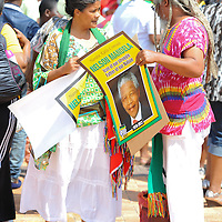 """A couple holding a commemorative poster during the City of Cape Town hosted concert at the 45000 seater Cape Town Stadium called """"Nelson Mandela - A life Celebrated"""". Concert goers walked the Fan Walk, called the """"Walk of Remembrance"""" for today and placed flowers at a memorial wall outside the stadium. Nelson Mandela was the first democratically elected president of South Africa."""