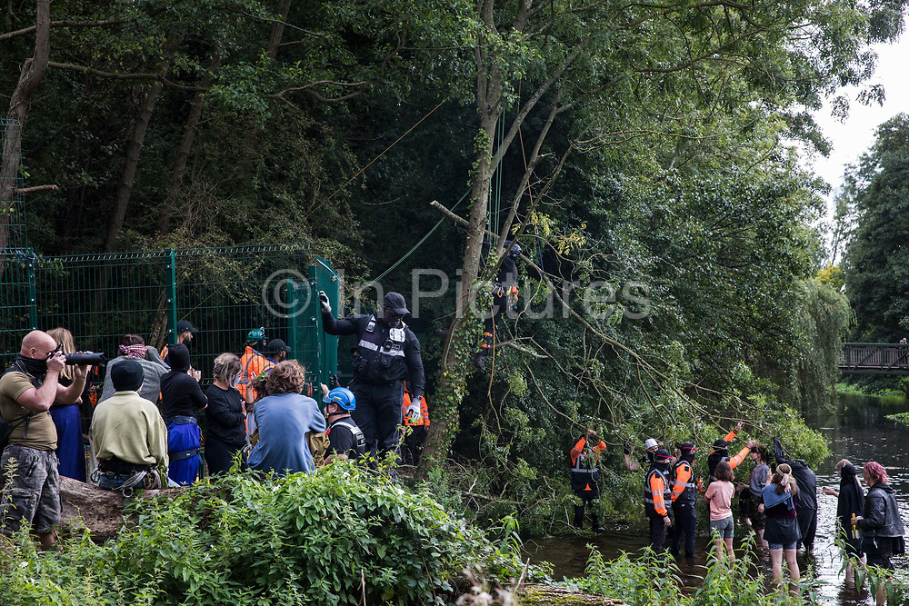 A large branch cut from a tree by a tree surgeon working on behalf of HS2 Ltd falls among security workers and HS2 Rebellion activists taking direct action to prevent or delay tree felling works in conjunction with the HS2 high-speed rail link in Denham Country Park on 7 September 2020 in Denham, United Kingdom. Anti-HS2 activists continue to campaign and take direct action against the controversial £106bn project for which the construction phase was announced on 4th September from a series of protection camps based along the route of the line between London and Birmingham.
