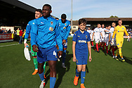 AFC Wimbledon defender Deji Oshilaja (4) and mascot during the EFL Sky Bet League 1 match between AFC Wimbledon and Portsmouth at the Cherry Red Records Stadium, Kingston, England on 13 October 2018.
