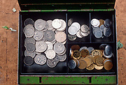 Months after the fall of the Berlin wall and the collapse of the communist GDR state German Democratic Republic, a 1990s tin of Deutschmark and Pfennig coins are on a cauliflower market stall, on 15th June 1990, in Leipzig, Eastern Germany.
