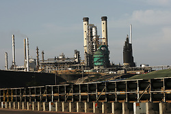 """PDVSA's oil refinery on the Paraguana Peninsula is the largest refinery in the world.  Since the removal of nearly 18,000 workers after an oil strike in Venezuela in 2002, PDVSA, the state run oil company has gone through drastic changes.  Struggling to replace the dismissed workers and return production to pre-strike quantities, PDVSA has also undertaken the financing and coordination of huge social programs.  PDVSA has invested billions of dollars in various education, food, medicine and infrastructure projects, calling itself the """"new"""" PDVSA."""