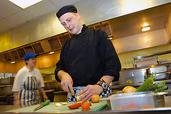 Chef prepares salad for hospital menu in NHS hospital kitchen West Yorkshire UK