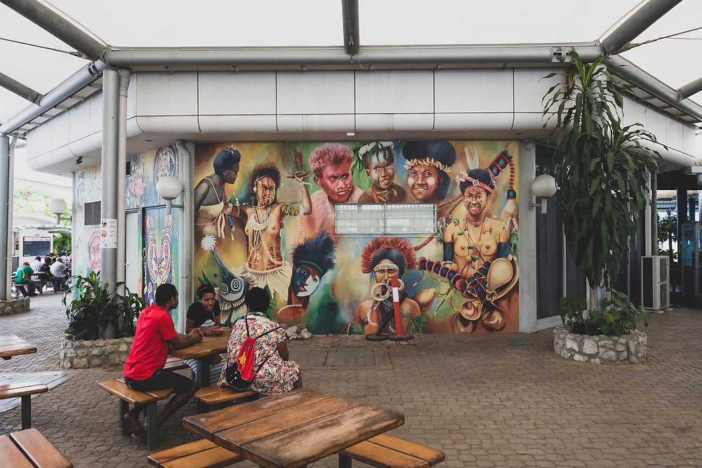 Port Moresby, Papua New Guinea - June 15, 2019: People sit out side the terminal near a beautiful mural at Jacksons International Airport in Port Moresby, Papua New Guinea