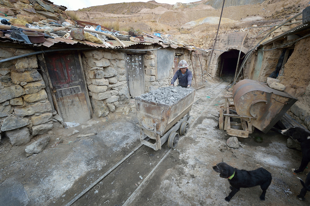 A miner moves an ore cart outside a mine in Potosi, Bolivia. The mine produces silver and other metals.