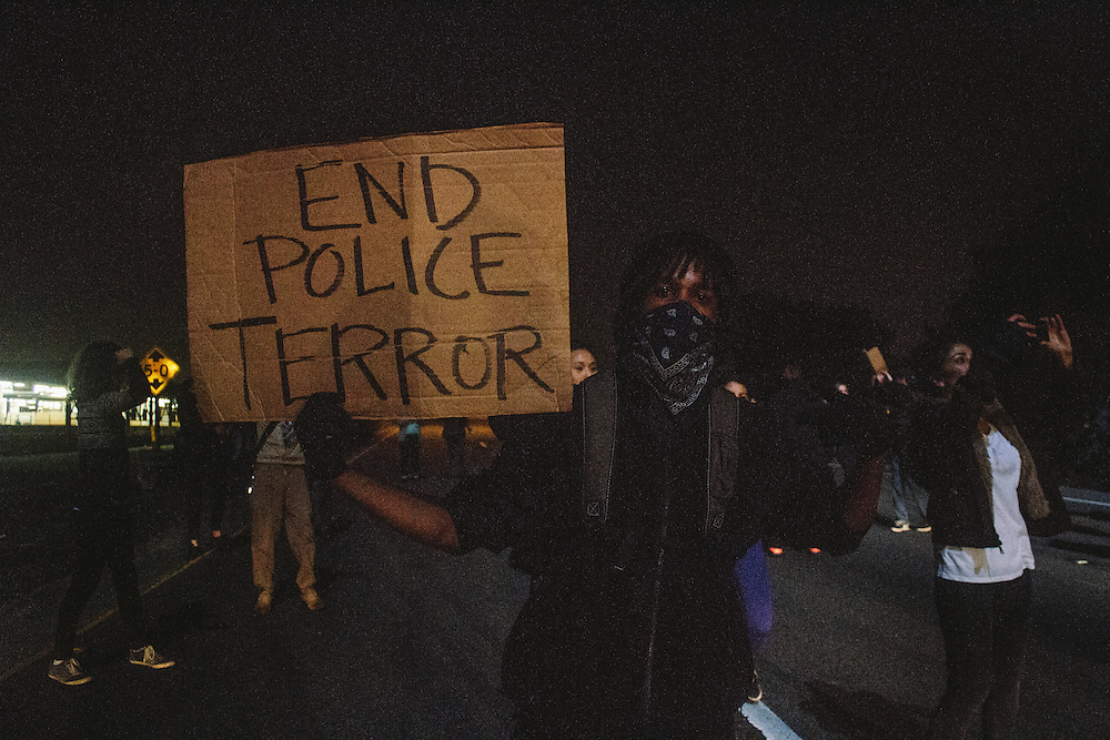 Protestor holding a poster in Oakland, CA 2014