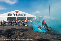 Stunt Rider Cole Freeman burns up another tire for the crowd at the Harley-Davidson downtown Sturgis display during the annual Black Hills Motorcycle Rally. SD, USA. August 9, 2014.  Photography ©2014 Michael Lichter.