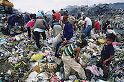 Asia, Philippines, Manilla, Smokey Mountain Rubbish dump. Children sifting throguh the rubbish. Thousands of poor and often indigenous people work sifting through the rubbish, recycling materials such as paper, various metal and plastic. They earn about $1 a day. The place is rife with disease. Photograph © Nigel Dickinson