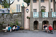 """Portmeirion, in North Wales, is a resort, where no one has ever lived. A self-taught Welsh architect named Sir Clough Williams-Ellis built it out of architectural salvage between the 1920s and 1970s, loosely based on his memories of trips to Portofino. Including a pagoda-shaped Chinoiserie gazebo, some Gothic obelisks, eucalyptus groves, a crenellated castle, a Mediterranean bell tower, a Jacobean town hall, and an Art Deco cylindrical watchtower. He kept improving Portmeirion until his death in 1978, age 94. It faces an estuary where at low tide one can walk across the sands and look out to sea. At high tide, the sea is lapping onto the shores. Every building in the village is either a shop, restaurant, hotel or self-catering accomodation. The village is booked out at high season, with numerous wedding receptions at the weekends. Very popular amongst the English and Welsh holidaymakers. Many who return to the same abode season after season. Hundreds of tourists visit every day, walking around the ornamental gardens, cobblestone paths, and shopping, eating ice-creams, or walking along the woodland and coastal paths, amongst a colourful assortment of hydrangea, rhododendrons, tree ferns and redwoods. The resort boasts two high class hotels, a la carte menus, a swimming pool, a lifesize concrete boat, topiary, pools and wishing wells. The creator describes the resort as """"a home for fallen buildings,"""" and its ragged skyline and playful narrow passageways which were meant to provide """"more fun for more people."""" It does just that.///Couples with young babies in pushchairs. Ornamental central gardens of Portmeirion village. Flanked by Dome Gallery, Gothic tower, Renaissance collonades, with lwans, flowerbeds, topiary, pools and fountains."""