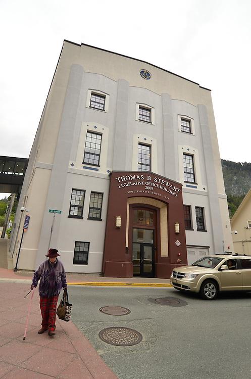 Woman walking across the street in front of the Thomas B Stewart Legislative Office Building in Juneau, Alaska.