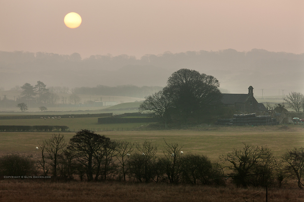 Early morning mist gardually disappears as the early morning sun hovers over a rural Anglesey landscape and old church, between Talwrn and Pentraeth on the isle of Anglesey. As the sun rose the fog became mist and then gradually evaporated and disappeared.