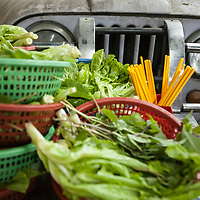 Plates of lettuce and herbs stacked up in front of a jeep at a restaurant in Saigon.
