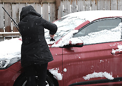 West Lothian Weather, Wednesday 3rd April 2019<br /> <br /> Pictured: A woman clears snow from her car<br /> <br /> Alex Todd   Edinburgh Elite media