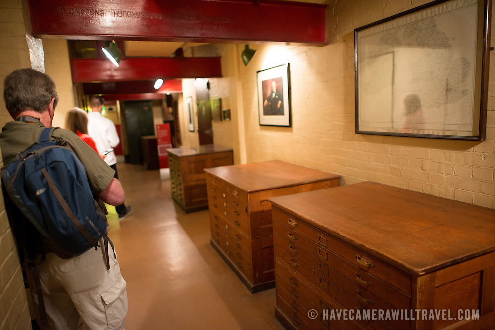 Visitors in a corridor in front of map drawers at the Churchill War Rooms in London. The museum, one of five branches of the Imerial War Museums, preserves the World War II underground command bunker used by British Prime Minister Winston Churchill. Its cramped quarters were constructed from a converting a storage basement in the Treasury Building in Whitehall, London. Being underground, and under an unusually sturdy building, the Cabinet War Rooms were afforded some protection from the bombs falling above during the Blitz.