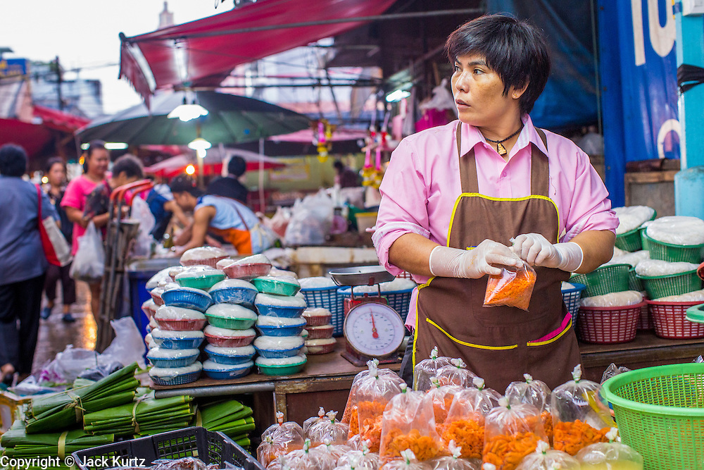 """03 OCTOBER 2012 - BANGKOK, THAILAND:     A vendor in Khlong Toey Market in Bangkok. Khlong Toey (also called Khlong Toei) Market is one of the largest """"wet markets"""" in Thailand. Thousands of people shop in the sprawling market for fresh fruits and vegetables as well meat, fish and poultry every day.        PHOTO BY JACK KURTZ"""