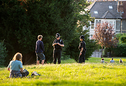 © Licensed to London News Pictures; 12/09/2020; Bristol, UK. Two police officers are seen in St Andrews Park talking to a young man, where large groups of young people are enjoying the early evening sunshine on the last weekend before new restrictions for the coronavirus covid-19 pandemic come into law in England. From Monday 14 September it will be illegal to meet up in groups of more than six people, known as the rule of six, in order to try and contain the spread of the coronavirus. Yesterday Bristol recorded the biggest daily increase in 10 weeks of new cases of coronavirus, and nationally, 3,539 new cases have been confirmed, the highest rise for four months. Photo credit: Simon Chapman/LNP.
