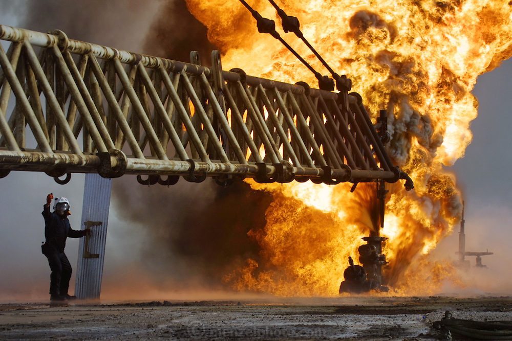"Firefighters from the KWWK (Kuwait Wild Well Killers) attempt to kill an oil fire in the Rumaila field by guiding a ""stinger"" that will pump drilling mud into the damaged well. A ""stinger"" is a tapered pipe on the end of a long steel boom controlled by a bulldozer. Drilling mud, under high pressure, is pumped through the stinger into the well, stopping the flow of oil and gas. The Rumaila field is one of Iraq's biggest oil fields with five billion barrels in reserve. Many of the wells are 10,000 feet deep and produce huge volumes of oil and gas under tremendous pressure, which makes capping them very difficult and dangerous. Rumaila is also spelled Rumeilah."