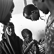 MSF doctors check 7-year-old Fatima Mohammed who weighs just 12 kgs, (half the recommended weight of a child her age, and the typical weight of a child of around 2 in the UK) at the MSF registration centre in Dagahaley refugee camp in the Dadaab, in northeastern Kenya. Hundreds of thousands of refugees are fleeing lands in Somalia due to severe drought and arriving in what has become the world's largest refugee camp. Photo: Sanjit Das/Panos
