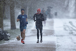 © Licensed to London News Pictures. 24/01/2021. London, UK. Members of the public exercise during a snow shower in Greenwich Park. Snow is expected for large parts of the UK and a yellow weather warning is in place in parts of England. Photo credit: George Cracknell Wright/LNP
