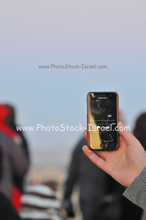 On December 10th 2011 a partial Lunar eclipse was visible. Photographed in Haifa, Israel Hand points a star map in a smartphone to the sky tracking the stars and the moon