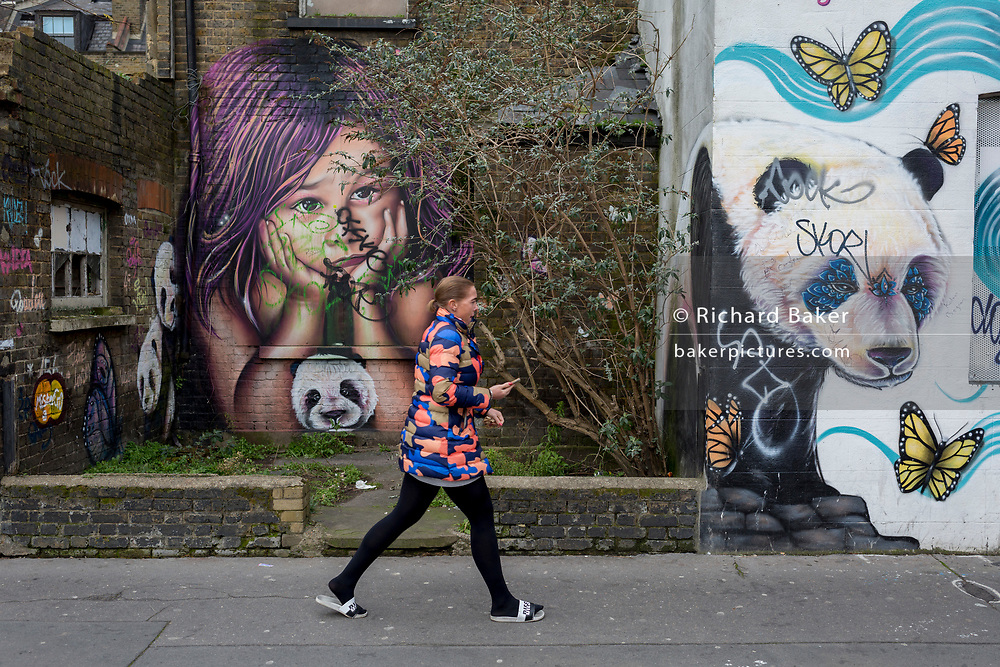 A lady walks past graffiti and urban artwork that features pandas and a child's face, on 20th January 2020, in Croydon, London, England.