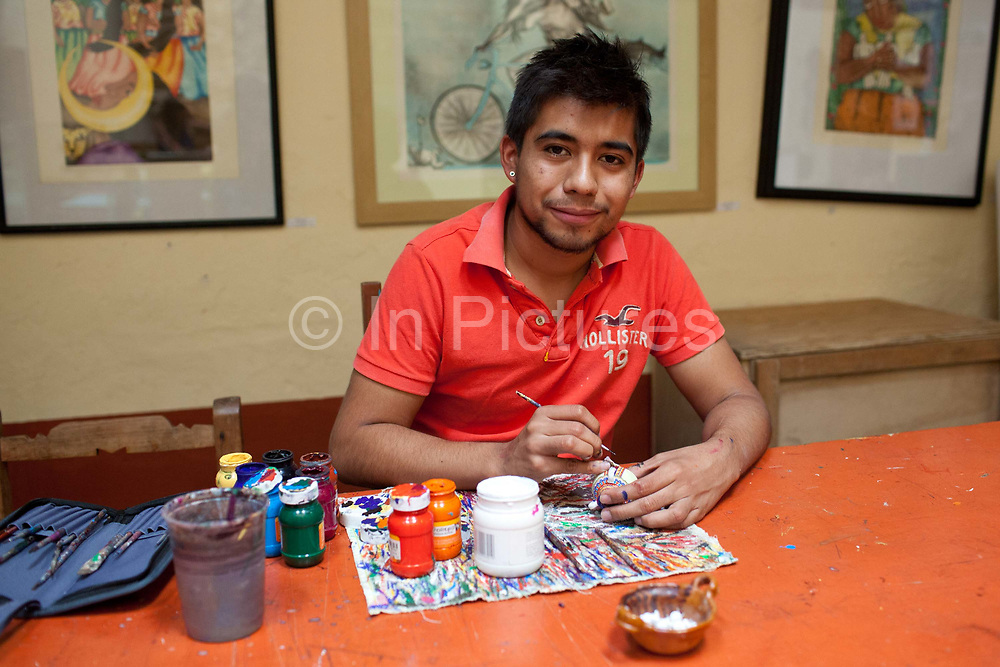 A local artist painting pots. Oaxaca in southern Mexico is known for its artisan communities, with each valley having a different specialism - weaving, pottery, wood carving.