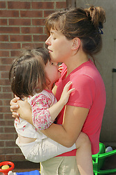 Mother hugging young girl with autism,