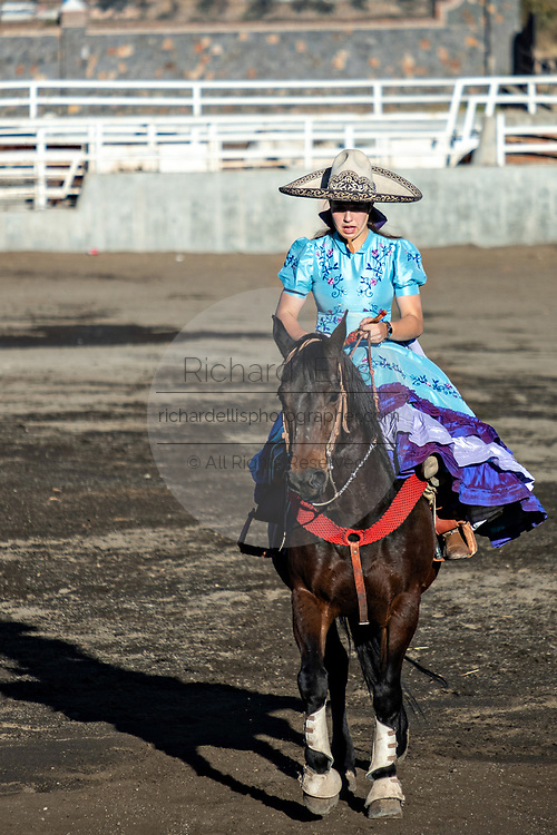 Saray Franco with the legendary Franco family of Charro champions, takes part in the Cala de Caballo riding sidesaddle in the traditional Adelita dress during a Mexican rodeo practice session in the Jalisco Highlands town of Capilla de Guadalupe, Mexico. Women participants in the traditional Charreada are called Escaramuza and perform precision equestrian displays riding sidesaddle and garbed in Adelita dress.