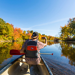 A man takes a cell phone photo while canoeing on the East Branch of the Penobscot River in Maine's Northern Forest. Fall.